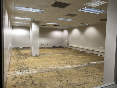 image is a photo of a room that has had the flooring removed. The walls are bare and a gray/off white color. A column stands in the middle of the room. Along the right side wall, wiring is exposed, and ceiling tiles have been removed, for construction purposes.